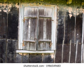 An old boarded up window in an old country house.