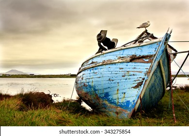 Old boat abandoned on the coastline in Ireland. Moody sky and run-down boat express lonliness and sadness.