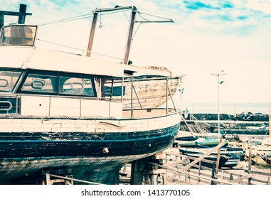Old boat in Acitrezza harbor with fisher boats next to Cyclops islands, Catania, Sicily, Italy.