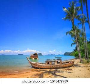 Old boat at beach with palm trees in Koh Yao Noi, Thailand