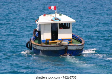 Old boat with cabin is sailing away, visible aft and Peruvian flag