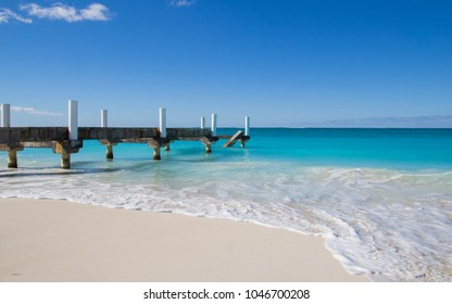 Old boat dock alongside the most majestic turquoise waters and white sands in Grace Bay Beach in Turks and Caicos Islands