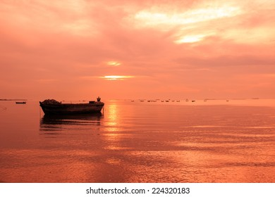 old boat in front of sunset background in red color tone