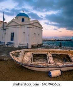 Old boat with greek church on a Mykonos island at sunset