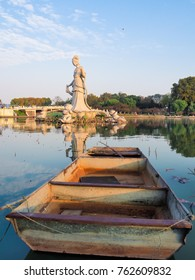 Old boat lying in front of the buddhist sculpture of Guanyin in the middle of a lotus pond in Xuanwu park Nanjing, China, during sunrise