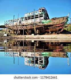 old boat, reflected in the water,