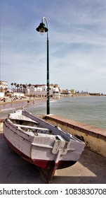 old boat stranded on the coast with lamppost next to the beach of la Caleta de Cádiz, spain,