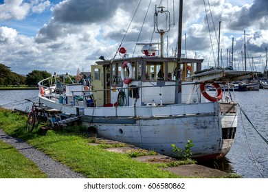an old boat that has see better days, moored with a bicycle parked beside it