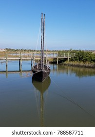old boat in water with boardwalk