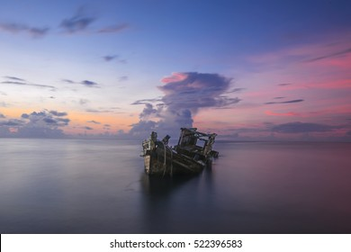 an old boat wreck at the sea of shore bank with colorful sunrise