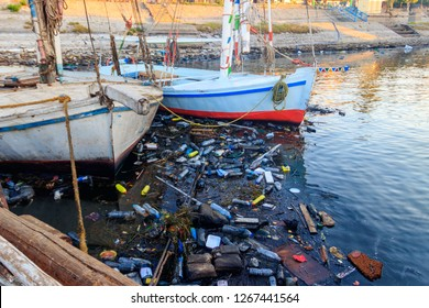 Old boats moored in dirty harbour. Pollution of river, sea, ocean water with waste, plastics garbage. Concept of pollution of ocean, sea and river coastline with plastic trash
