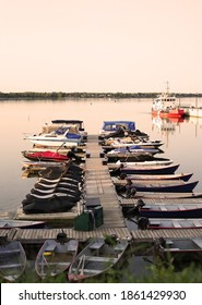 Old boats moored at a wooden pier on the lake, sunset, Chambly, Quebec, Canada