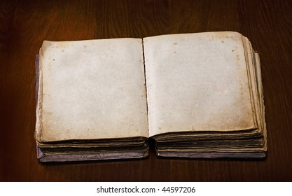 old book with blanked pages over a wooden table