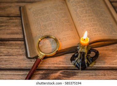 Old book candle on a wooden background