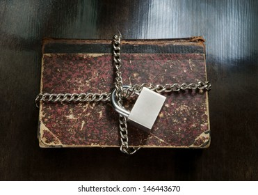 Old book with chain and padlock on wooden table