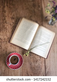 an old book and cup of coffee on a wooden table
