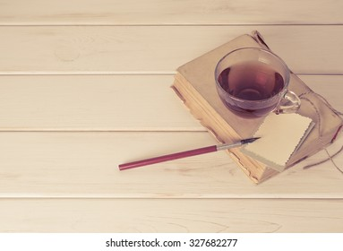 Old book with decorative greeting card, nib pen and cup tea on white wooden boards