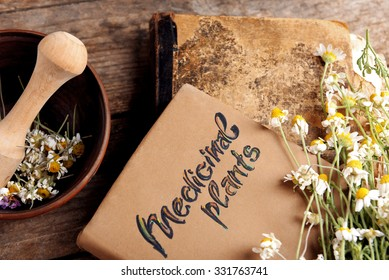Old book with dry flowers in mortar on table close up