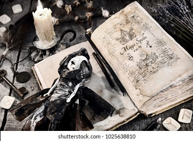 Old book with evil spells, scary doll, rune and burning candle on planks. Halloween, occult, esoteric and wicca concept. Vintage background