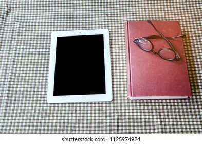 old book with eye glasses and laptop computer