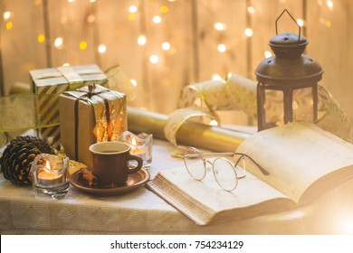 Old book with eyeglasses. Christmas decoration on background. Cup of coffee