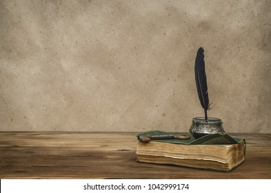 Old book and feather pen with inkpot and rusty key on retro wooden table background with copy space. Writer table concept. Education. Back to school. Memoirs.