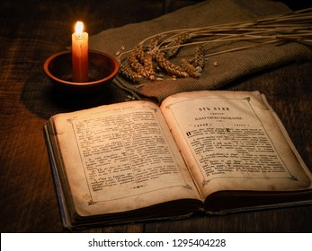 Old book Gospel in Russian and Old Slavonic languages on a wooden table in the light of a candle and ears of wheat on linen fabric 01.26.2019 Izyum Ukraine
