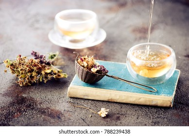 Old book, herbal tea and dried herbs and flowers