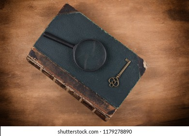 Old book, a key and a magnifying glass on the book against a worn wooden background with dark edges (top view) as the crime story concept