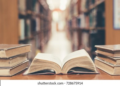 Old book in library with open textbook, stack piles of literature text archive on reading desk, and aisle of bookshelves in school study class room background for academic education learning concept