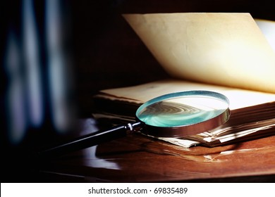 Old book and magnifier glass on a dark background as a symbol of knowledge and science