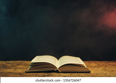 Old book on a oak wooden table. Background of blue and red smoke.