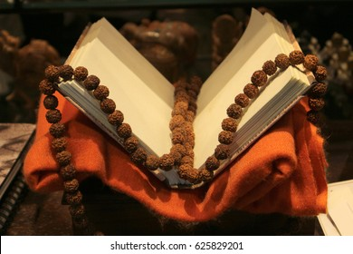 An old book on a red cloth with Rudraksha beads.