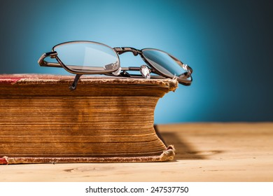 old book on wooden table and blue background