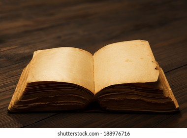 old book open blank pages, empty yellow paper on dark brown wooden table
