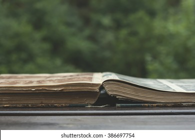 old book open on a garden wooden table