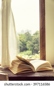 Old book open on wooden desk and window curtain vintage style