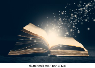 Old book opened  and light particles on dark bg photo