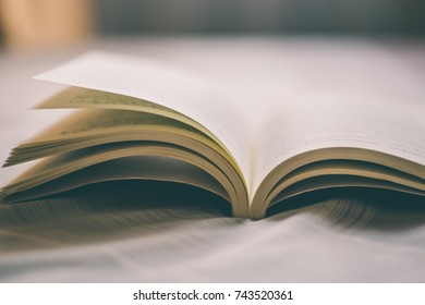 Old book opened on the bed with vintage tone