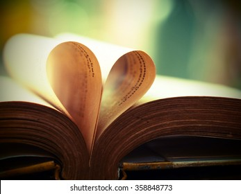 Old book page decorate to heart shape for love in valentine day with blurred background and vintage color tone style. Composition of love with open book heart