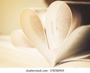 Old book page decorate to heart shape for love in valentine day with blurred background and vintage color tone style. Selective focus.
