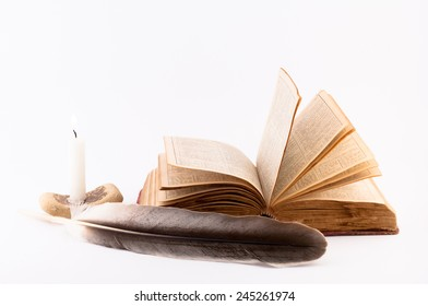 old book pages dissolved, candle and feather on a white background