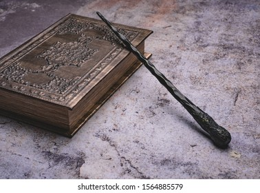 Old book with spells and magic wand on gray background. Copy space for text