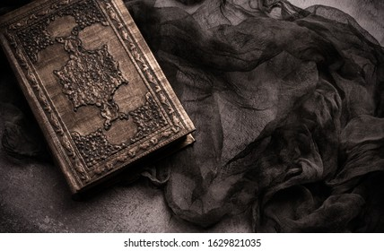 Old book with spells and magic wand on gray background with witch rag. Copy space for text