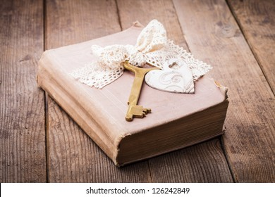 Old book with vintage key and wooden heart, memories concept