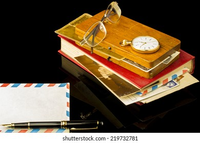 Old book and wood box with old pictures, glasses, pen, pocket watch all on a black background with blank space