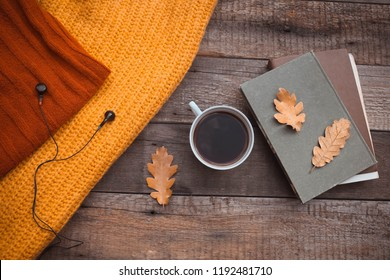 Old book,earphone , autumn leaves on wooden background. Concept autumn. Top view