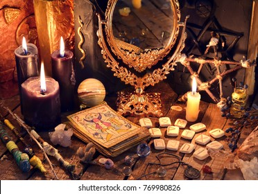 Old books, black candles, mirror, tarot cards and runes on witch table. Occult, esoteric, divination and wicca concept. Mystic and vintage background