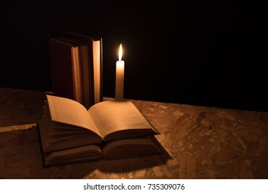 Old books and burning candle on a wooden table on a dark night