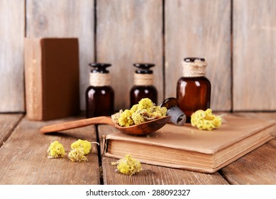 Old books with dry flowers and bottles on wooden background